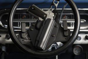 Gun in holster on car steering wheel